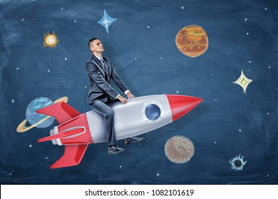 A serious businessman rides a silver and red rocket among the drawings of planets and stars. Achieve your dream. Business space. Corporate universe.