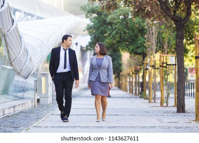 Serious businessman sharing ideas with colleague during stroll. Confident business people walking over street and talking. Break concept