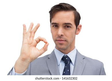 Serious businessman showing ok sign against white background