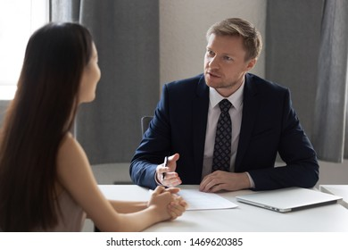 Serious businessman sit at office desk talk interview young woman work candidate in office, concentrated male employer speak with female job applicant during hiring process. Recruitment concept