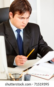 Serious businessman sitting at office desk and intently looking at document