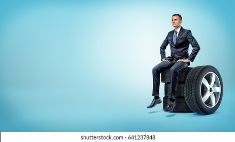 A serious businessman sitting on a stack of car tires with hands on his hips. Repair shop. Car service. Spare parts reselling.