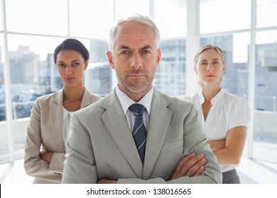 Serious businessman standing in front of colleagues with arms crossed