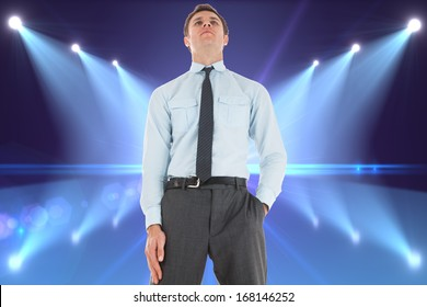 Serious businessman standing with hand in pocket against cool nightlife lights