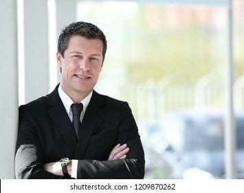 serious businessman standing near window in office.