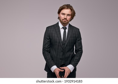 serious businessman standing with smartphone looking at camera, having confident look. caucasian bearded male in suit isolated
