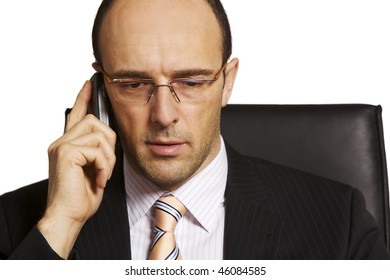 Serious businessman in suit sitting at desk in office  talking on cell phone, white background