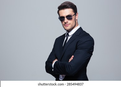 Serious businessman in sunglasses standing with arms folded over gray background