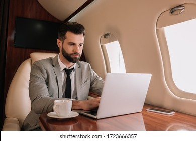 serious businessman typing on laptop near cup of coffee in private plane
