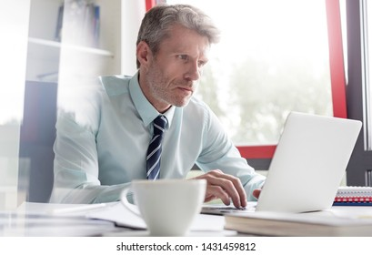 Serious businessman using laptop at desk in office