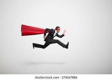serious businessman wearing like superhero very fast running over light grey background