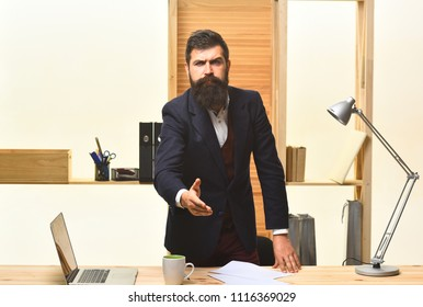 Serious businessman welcoming. Handshaking. Portrait of considerable bearded businessman. Serious businessman in suit. Man offering his hand to welcomed. Handsome bearded office worker.
