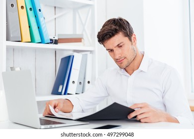Serious businessman working with documents in folder at workplace in office
