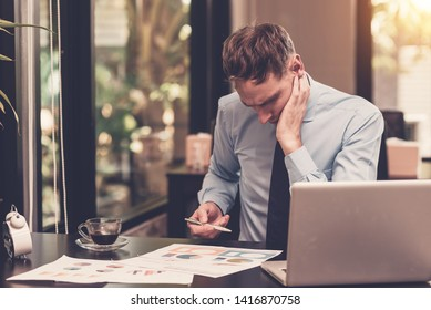 Serious businessman working with laptop and business documents on the table. Businessman concept
