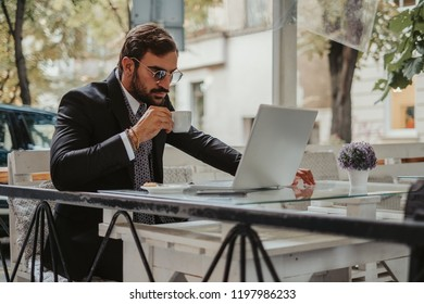 Serious businessman working on a laptop and drinking coffee outside in a cafe