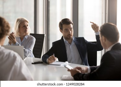 Serious businessmen businesswomen gathered in boardroom discuss new ideas for company growth, discover new ways exploring additional business opportunities solve problems related with small business