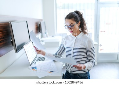 Serious businesswoman dressed casual standing in modern office and comparing paperwork.