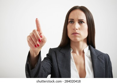 serious businesswoman holding her forefinger like pushing button on virtual screen over light grey background