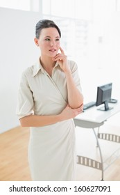 Serious businesswoman looking away as she stands in the office