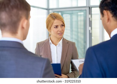 Serious businesswoman looking at her colleague during conversation