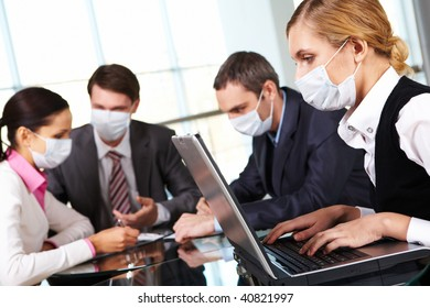 Serious businesswoman in protective mask looking at screen of laptop in working environment