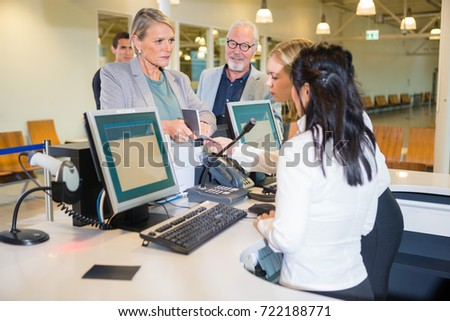 Serious Businesswoman Showing Passport To Staff At Airport