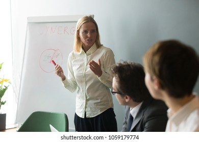 Serious businesswoman speaking giving presentation to business group working on flipchart, team leader coaching presenting marketing training, explaining corporate goals or sales management strategy
