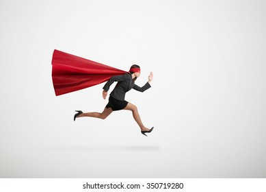 serious businesswoman wearing like superhero very fast running over light grey background