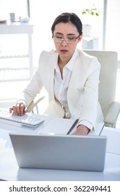 Serious businesswoman working at her desk in her office