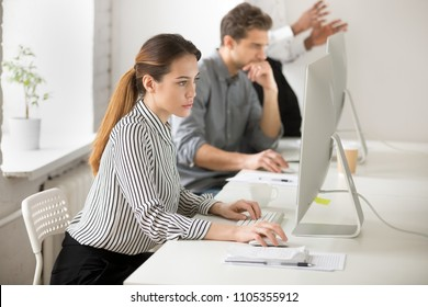 Serious businesswoman working at personal computer in coworking space, writing emails to business clients, thoughtful worker browsing internet, reading financial news, checking company statistics