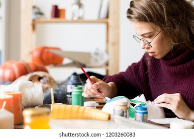 Serious busy attractive young craftswoman in glasses sitting at table and elaborating design of Halloween mask, she painting mask in art studio