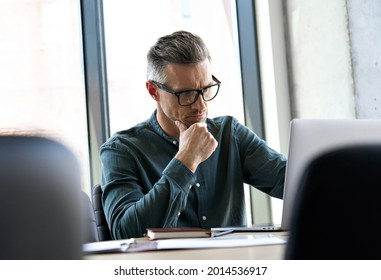 Serious busy elegant mature businessman corporate leader successful ceo executive manager thinking of online business planning financial market strategy, using laptop computer sitting at office table.
