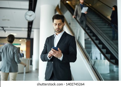 Serious busy handsome young businessman with beard standing in airport hall and browsing internet on gadget while checking flight schedule