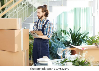 Serious busy handsome young mover writing notes in sketchpad while examining packaged boxes stacking in space of new restaurant