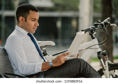 Serious busy man searching job in newspaper while sitting on bench in park. Concentrated modern male analyst with bicycle reading article in morning newspaper. Business lifestyle concept