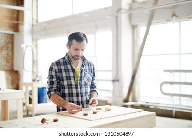 Serious busy middle-aged workman with stubble standing at table and comparing small wooden details while making kids toy in workshop