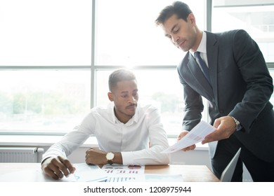 Serious busy multi-ethnic business colleagues analyzing charts and discussing company development in modern office