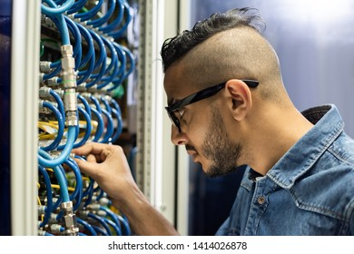 Serious busy young Arabian engineer with hipster hairstyle and beard standing by cabinet of supercomputer and connecting broadband cables