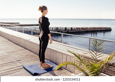 Serious calm attractive young woman in sports clothing keeping eyes closed and meditating while preparing for standing on board with sharp nails outdoor against the sea on wooden fitnes terrace