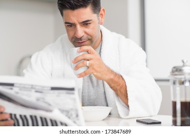 Serious casual man with coffee cup reading newspaper in the kitchen at home