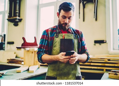 Serious cauacan male owner of workshop checking messages from clients for repair furiniture using mobile phone, bearded foreman in apron standing near working place with smartphone conneccted to wifi
