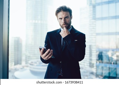 Serious caucasian bearded male manager in suit puzzled on new app for banking on mobile phone making transactions via device in office, confident businessman waiting for call holding smartphone