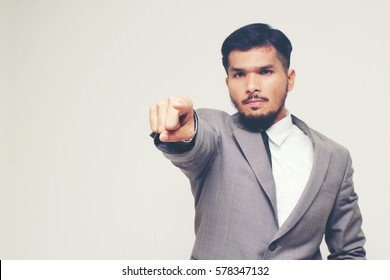 Serious Caucasian businessman with black hair in business formal outfit waving finger with copyspace.