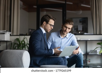Serious Caucasian businessmen sit in office look at laptop screen discuss business project or idea on gadget, male colleagues employees busy brainstorming working together cooperating on computer