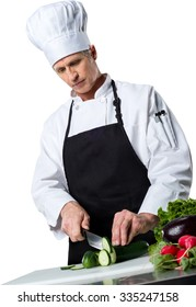 Serious Caucasian Chef  in uniform cutting fruits and vegetables on a chopping board - Isolated