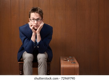 Serious Caucasian male with chin in hands and suitcase