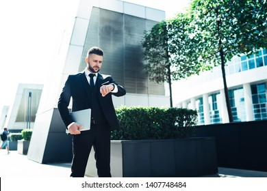 Serious Caucasian male entrepreneur with laptop device in hand harry up for business meeting in Manhattan office building checking time while late, handsome man looking on wristwatch outdoors