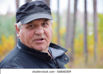 Serious caucasian old man in the autumn forest