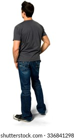 Serious Caucasian young man with short black hair in casual outfit with hands in pockets - Isolated