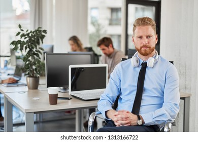 Serious CEO in formal wear and with headphones around neck sitting in chair and looking at camera. Office interior.